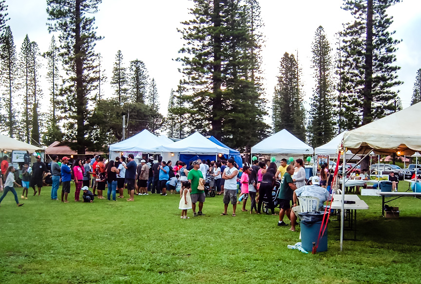Photo of Pineapple Festival with tents, vendors and Lanai community members in Dole Park.