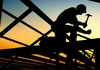Photo of construction worker silhouetted on building frame.