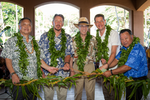 Photo of Larry Ellison and other guests wearing lei and holding maile lei in Four Seasons lobby.