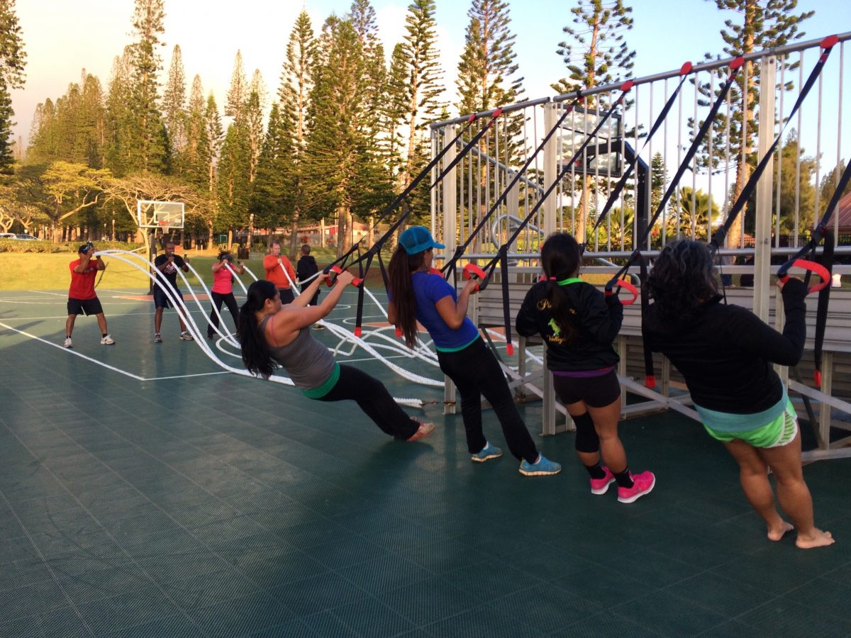 Group of women exercising outdoors at park.
