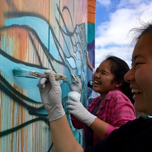 Close up photo of two girls painting mural.
