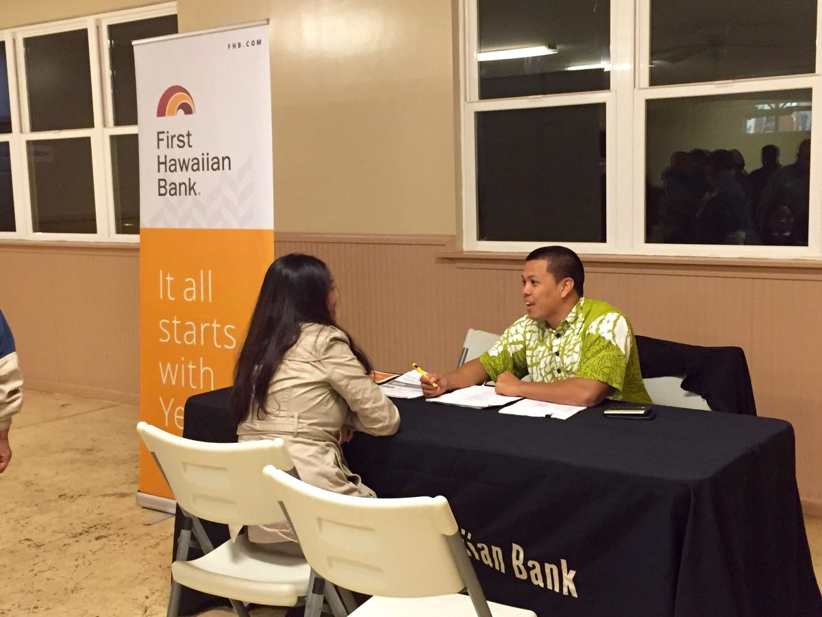 Photo of Lanai bank representative sitting down at desk meeting with person at homebuyers fair.