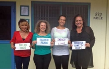 Photo of Hospice Hawaii-Lanai employees holding signs in front of building.