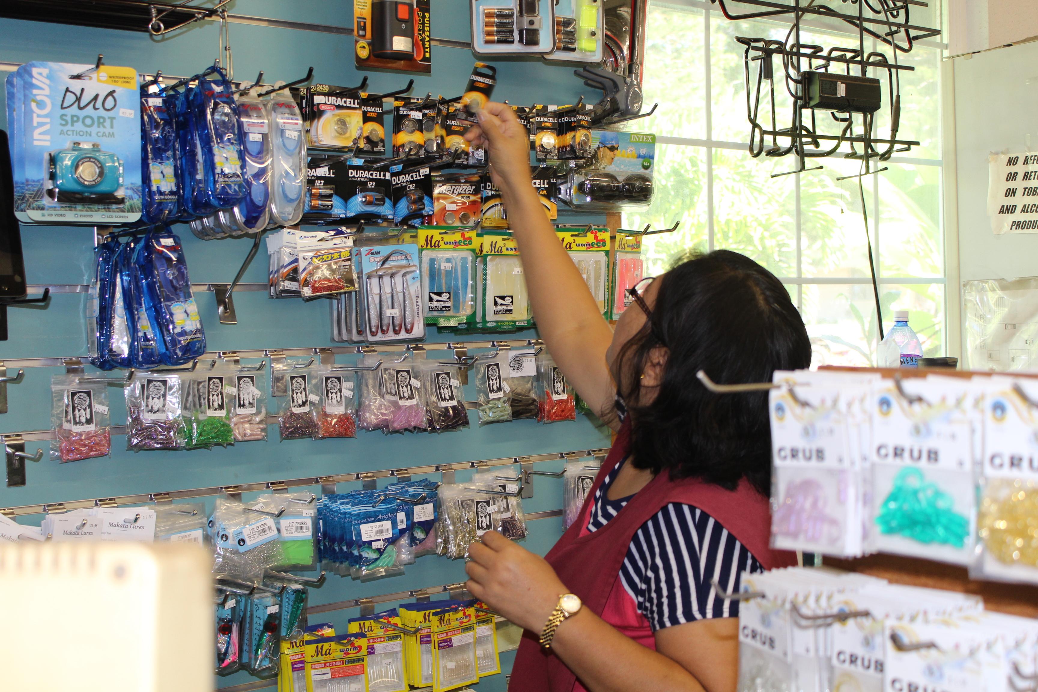 Photo of employee stocking shelf at Pine Isle Market on Lanai.