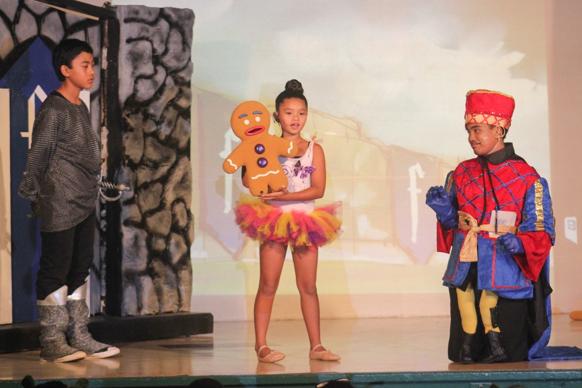 Photo of Lanai children actors in Pinocchio and three pigs costumes performing Shrek onstage.