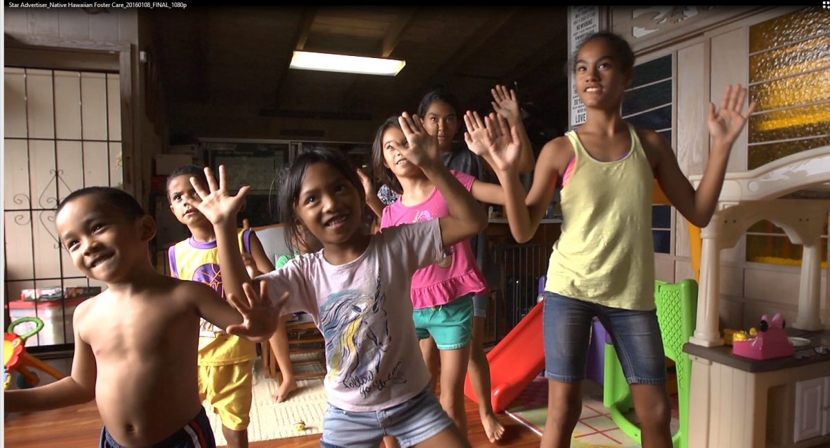 Photograph of children playing in home with hands up.
