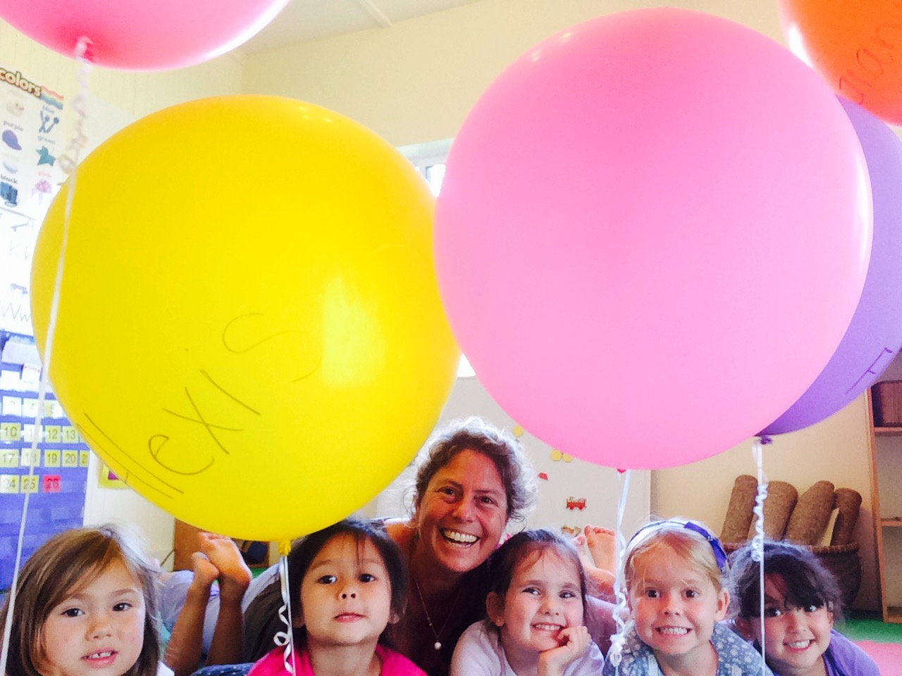 Teacher and young children holding balloons.