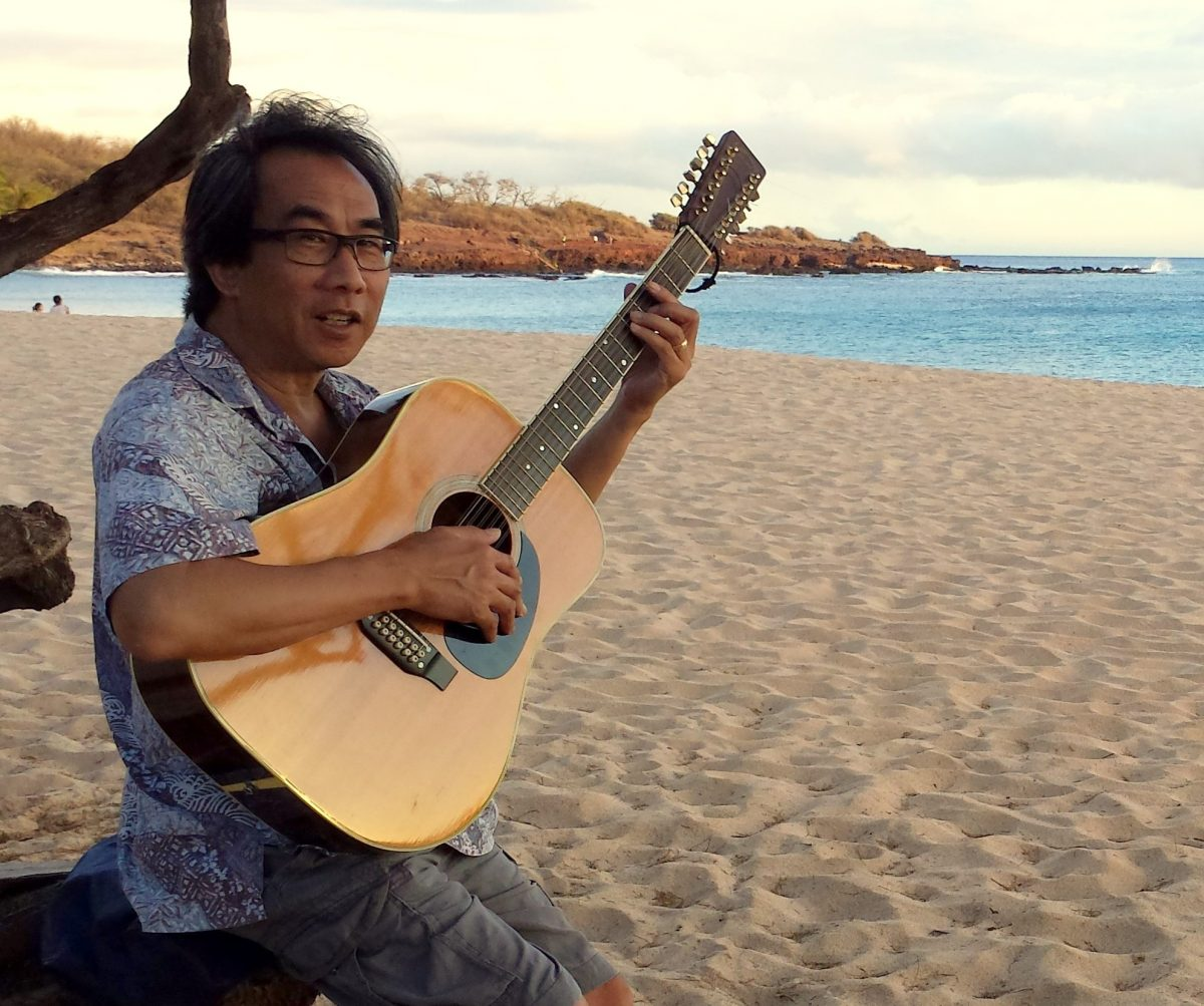 Photo of Lanai teacher Peter Palisbo playing guitar on Hulopoe Beach.