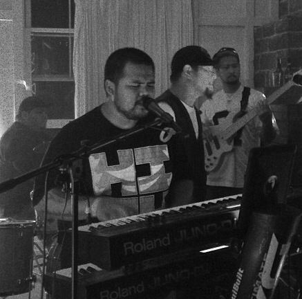 Black and white photo of Lanai band Redkrown playing onstage.