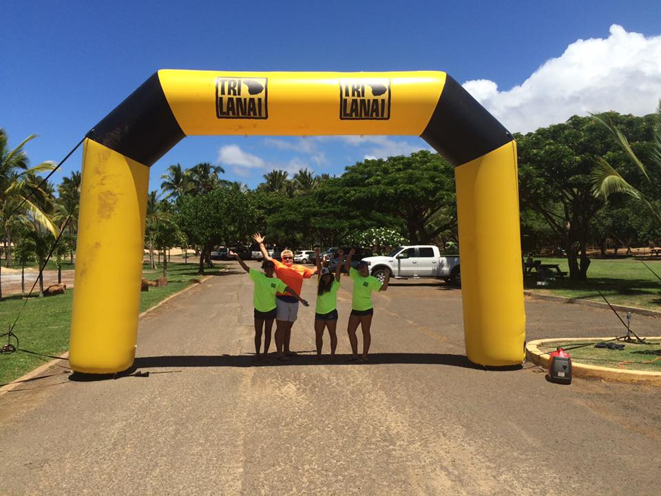 Photo of TriLanai athletes posing under finish line arch on race course in Lanai.