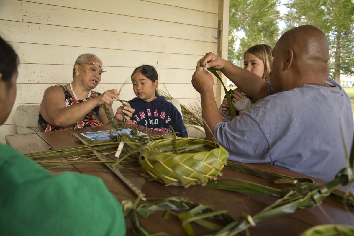 Photo of man and women showing leaf weaving techniques to children.
