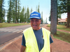 Photo of Lanai crossing guard Wilfred Aoki wearing yellow vest and standing outside.