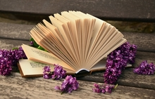 Photo of open book with flowers on a wood table.