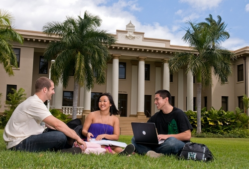 Photo of college students sitting on lawn in front of Hawaii college building.