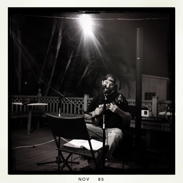 Photo of Lanai vice principal Jerod Savage singing and playing music at coffee shop.